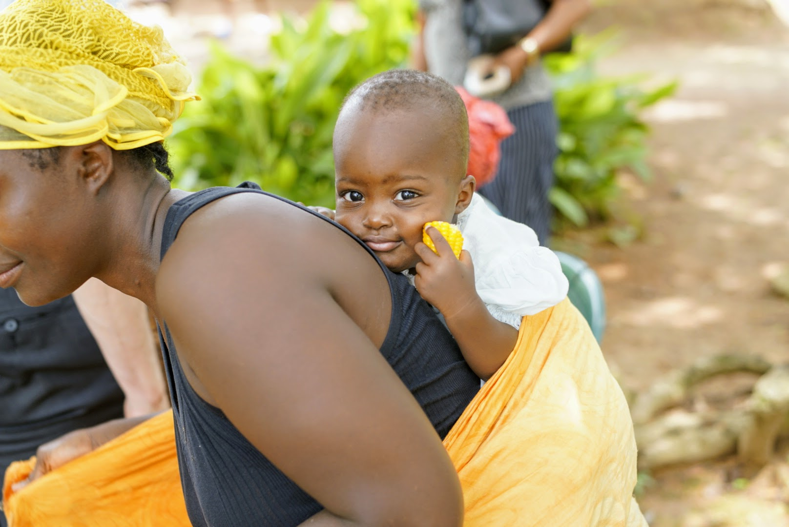 A mother carries her baby on her back in Sierra Leone.