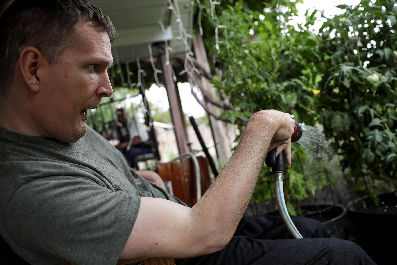 Orin Voorheis waters plants outside his home in Pleasant Grove, Utah, on Tuesday, July 10, 2018.