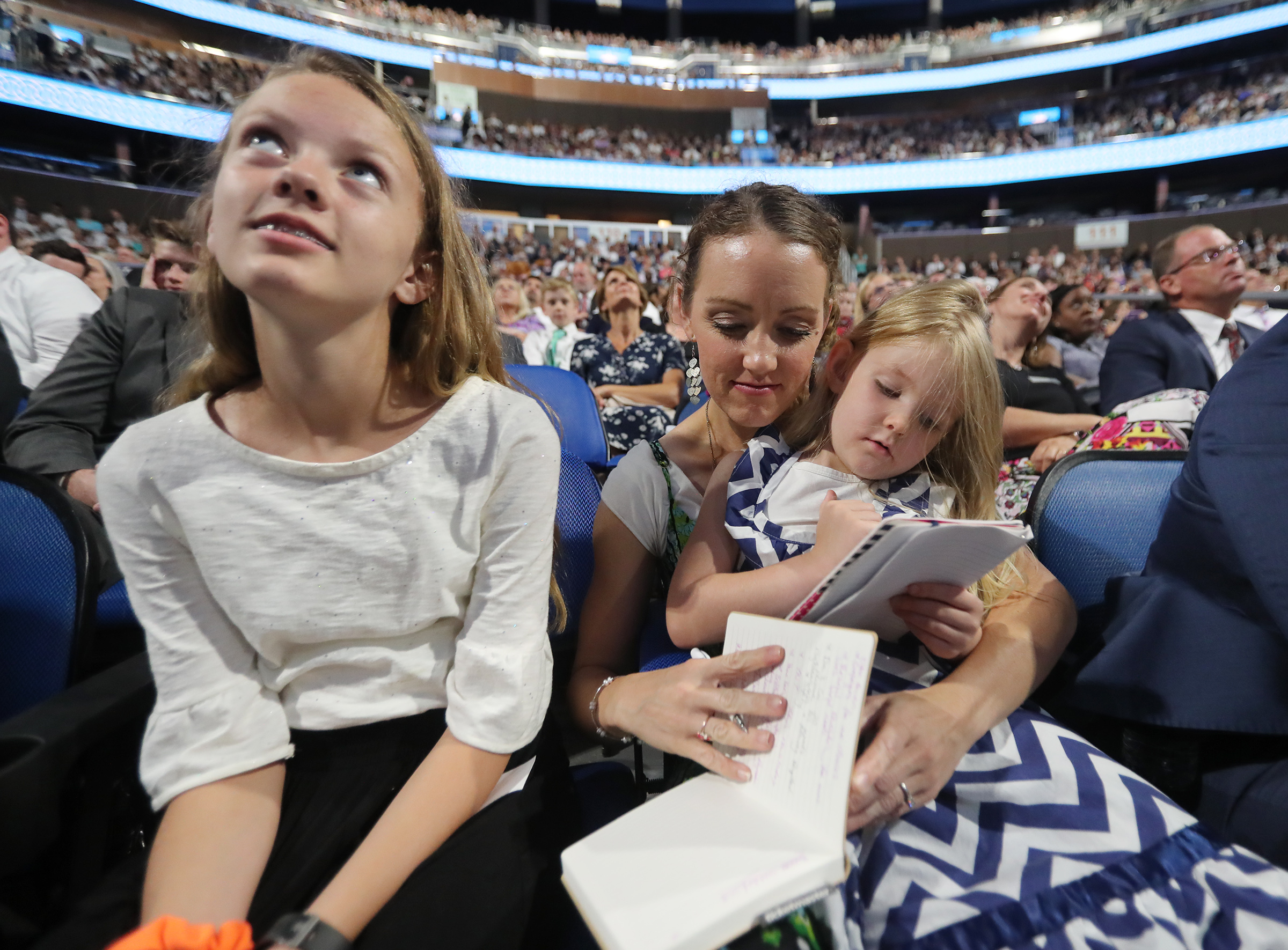 Juliette Ebbert, sits with her mom, Cheri Ebbert, and sister Sadie Ebbert and listen as President Russell M. Nelson and others speak at the Amway Center in Orlando, Florida, on Sunday, June 9, 2019.