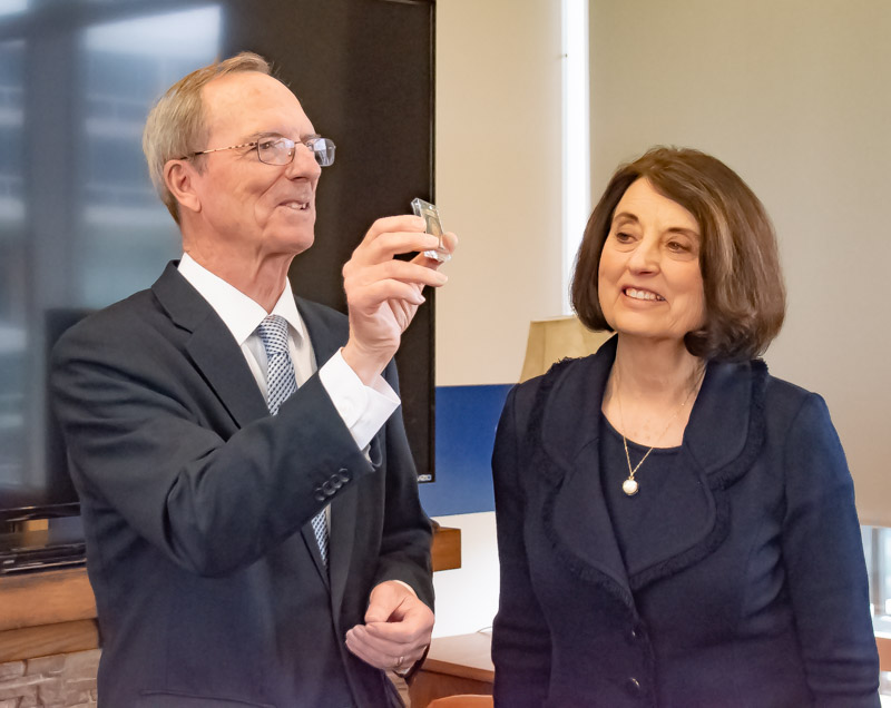Brother Tad R. Callister shows the special unit coin presented to graduating seniors during a reception held prior to the Baccalaureate service on May 20.