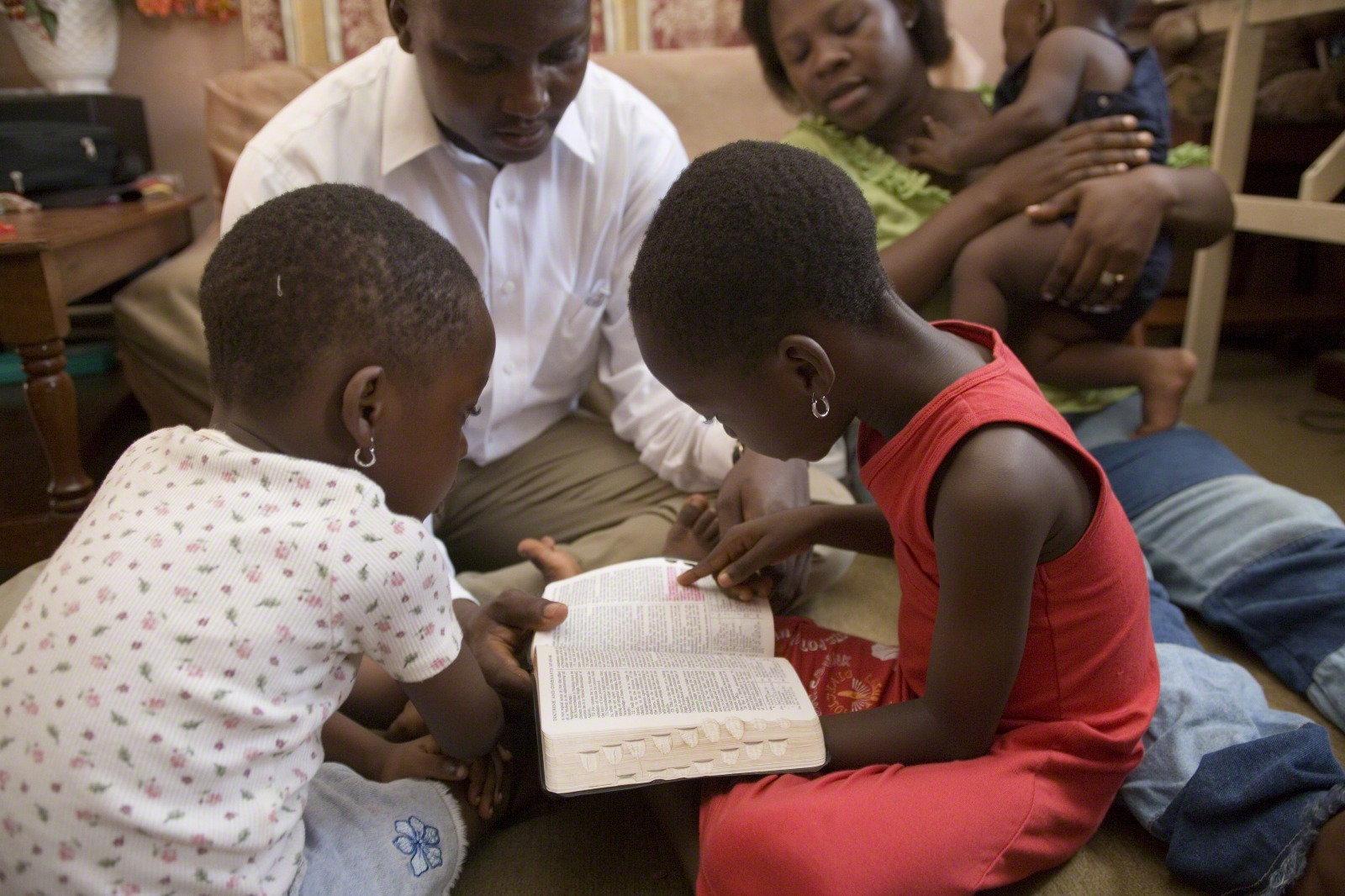 A father helps his two daughters read from the scriptures.