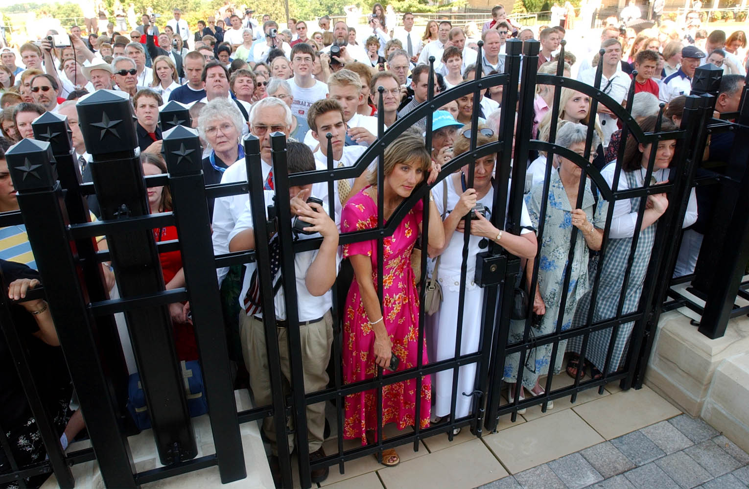 Crowds press against the temple gate listening to President Hinckley at a press conference at the Nauvoo LDS Temple June 27th, 2002.