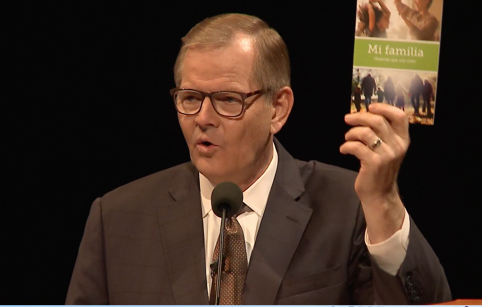 """Elder Gary E. Stevenson of the Quorum of the Twelve Apostles speaks about family history tools while holding a """"My Family"""" booklet. The image is from a screenshot from the Feb. 28 broadcast of the instruction meeting to ward and stake leaders and members with temple and family history work callings and responsibilities."""