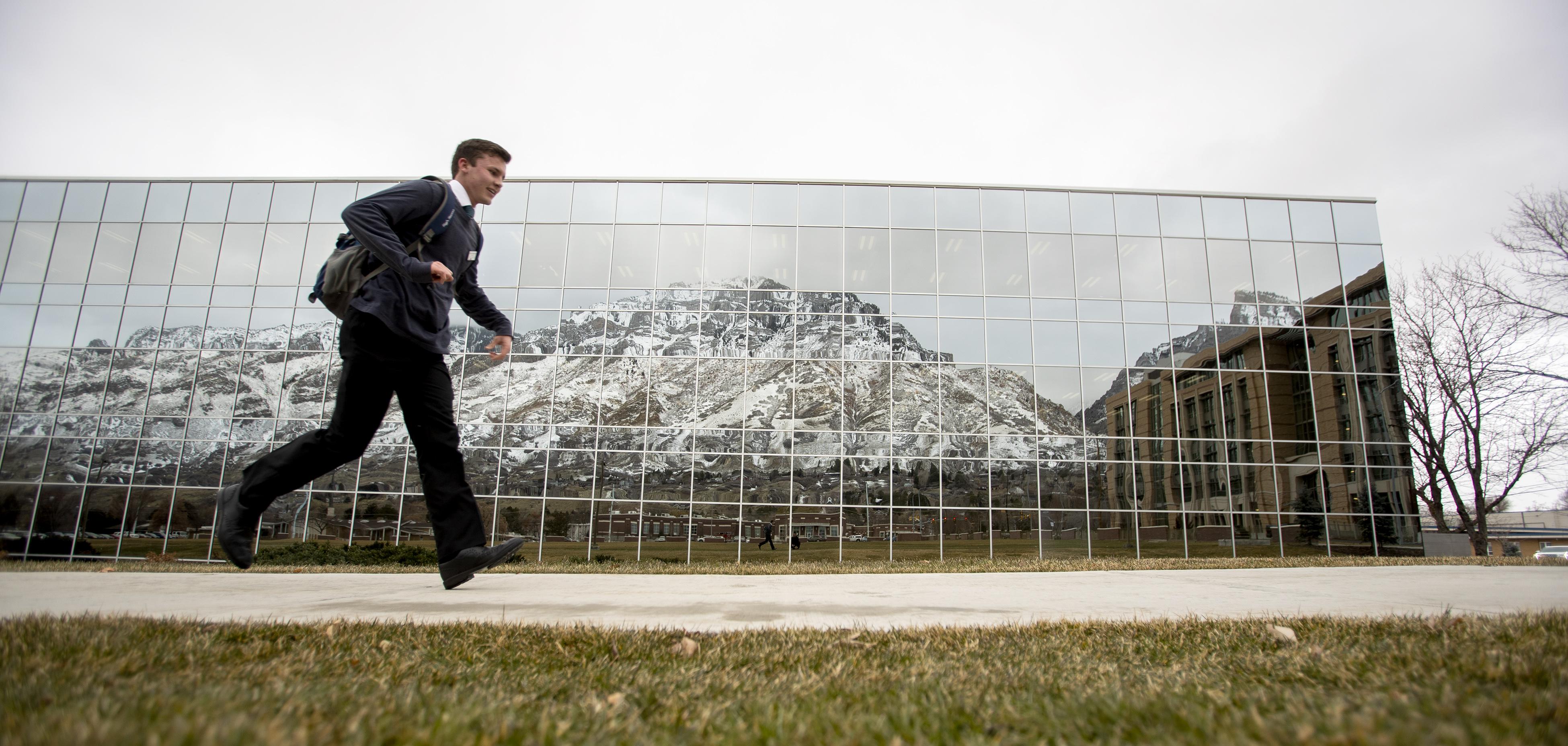 A student runs on the sidewalk past the Caroline Hemenway Harman Building at BYU in Provo, Utah, on Tuesday, Feb. 5, 2019.