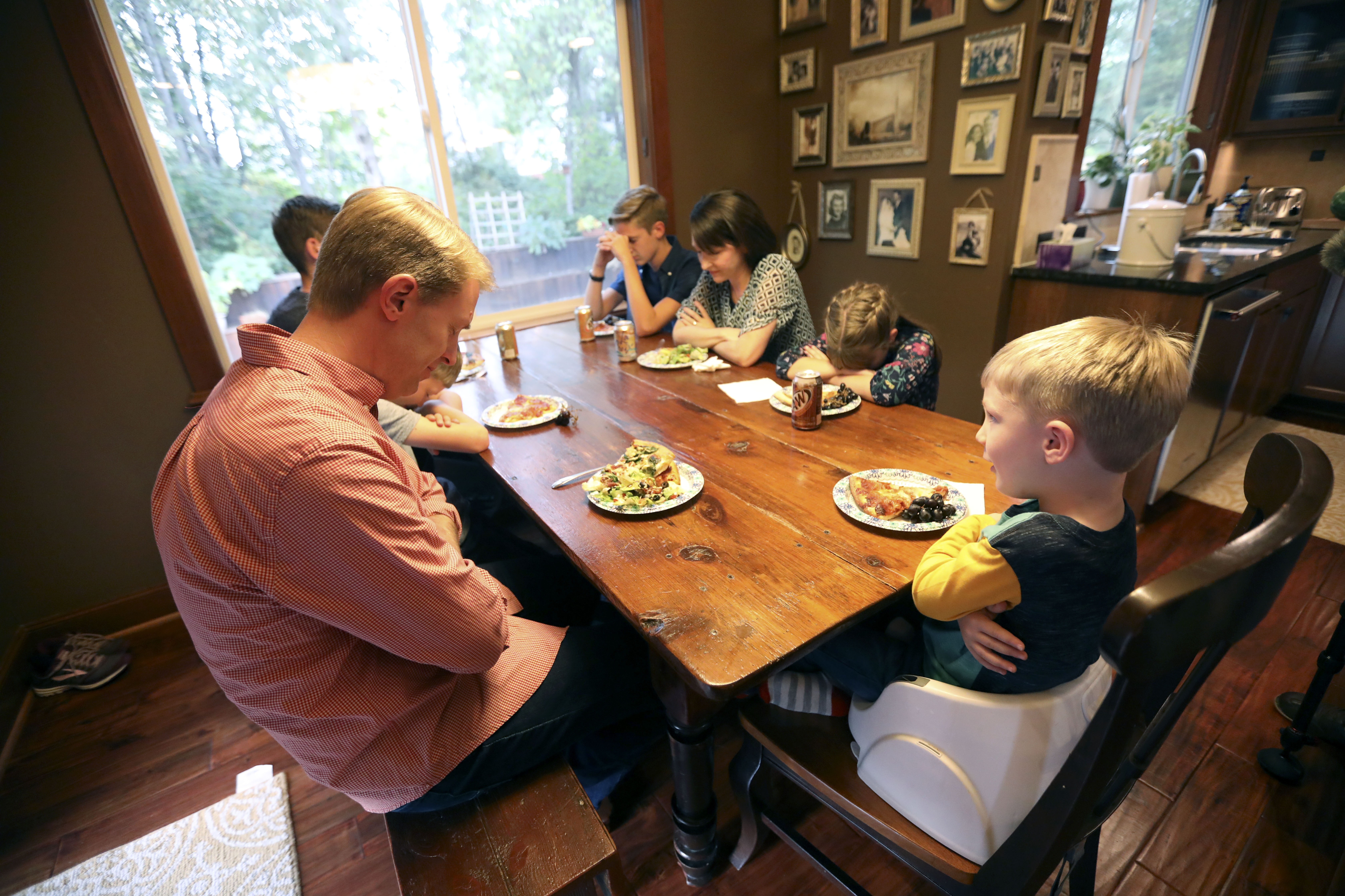 Daniel Allen, right, leads him family in prayer before dinner at home in Renton, Wash., on Friday, Sept. 14, 2018. His father, Justin Allen, is on the left. Jonathan, Alexis and Emilia Allen are on the right side of the table.