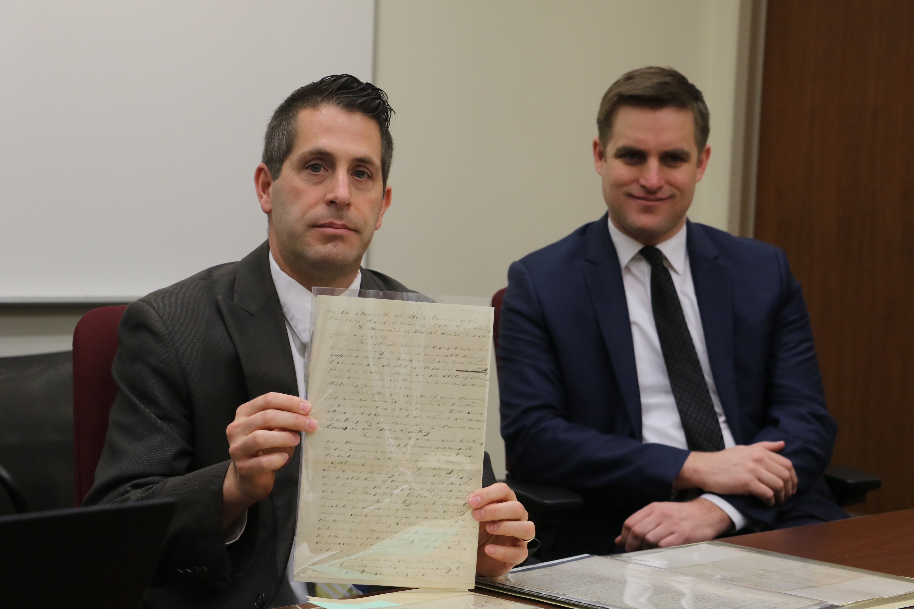 Matthew C. Godfrey, with fellow volume editor Spencer W. McBride in background, displays petition from Joseph Smith to the high council in Nauvoo. It is one of 129 documents contained in latest Joseph Smith Papers release.