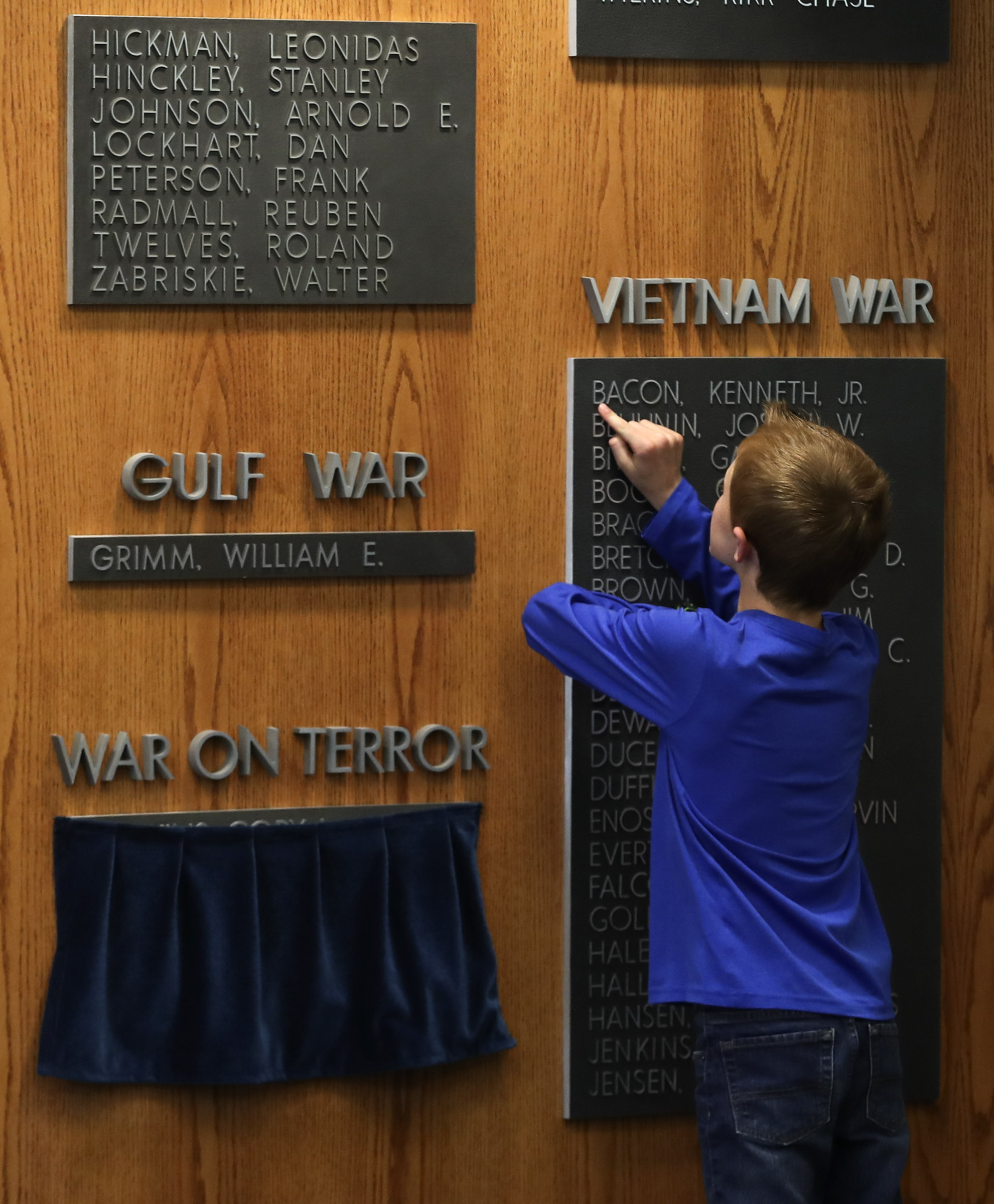Jacob Taylor looks at names on Reflection Room Memorial Wall in the Wilkinson Center prior to a ceremony where the name of his father, Maj. Brent Taylor, was added to the wall on the BYU campus in Provo on Thursday, May 23, 2019. Taylor was killed in Afghanistan in 2018.