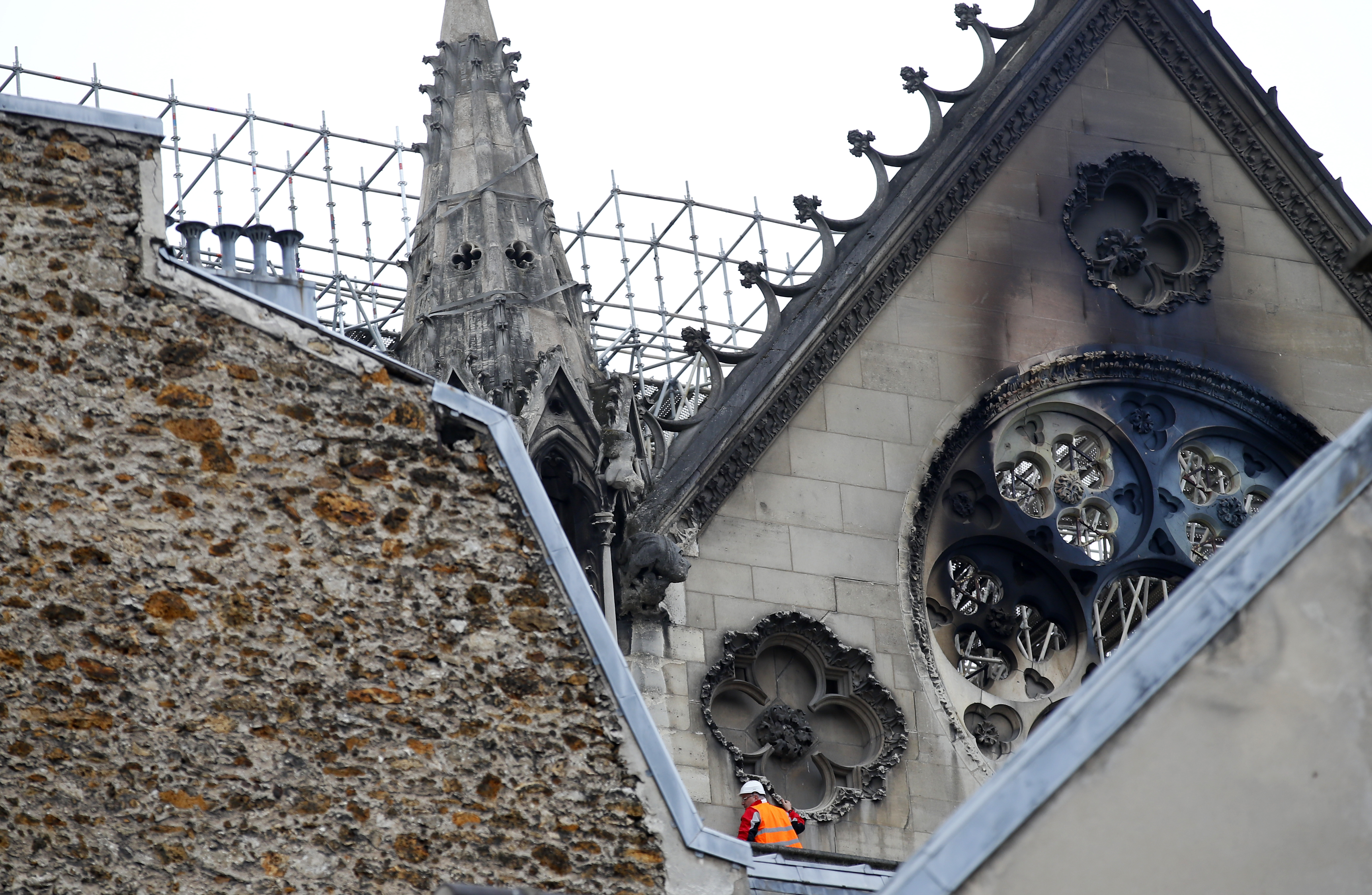 A man is pictured near chared glass windows of the Notre Dame cathedral Tuesday April 16, 2019 in Paris. Firefighters declared success Tuesday in a more than 12-hour battle to extinguish an inferno engulfing Paris' iconic Notre Dame cathedral that claimed its spire and roof, but spared its bell towers.