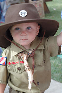 Youngster dons a wide-brimmed hat and Scout regalia during the traditional children's parade.