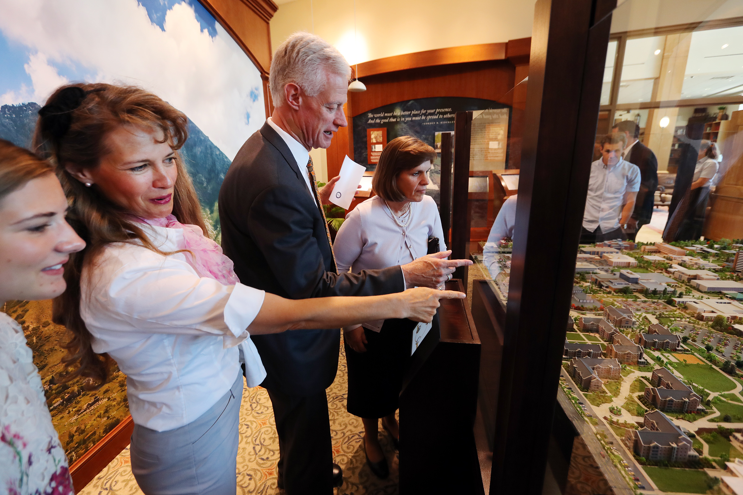 Mary Sorensen, her mother Stephanie Sorensen, President Kevin J Worthen and his wife Peggy look at the Easter egg placed on the map as BYU unveils a highly-detailed campus diorama on Tuesday, July 2, 2019.