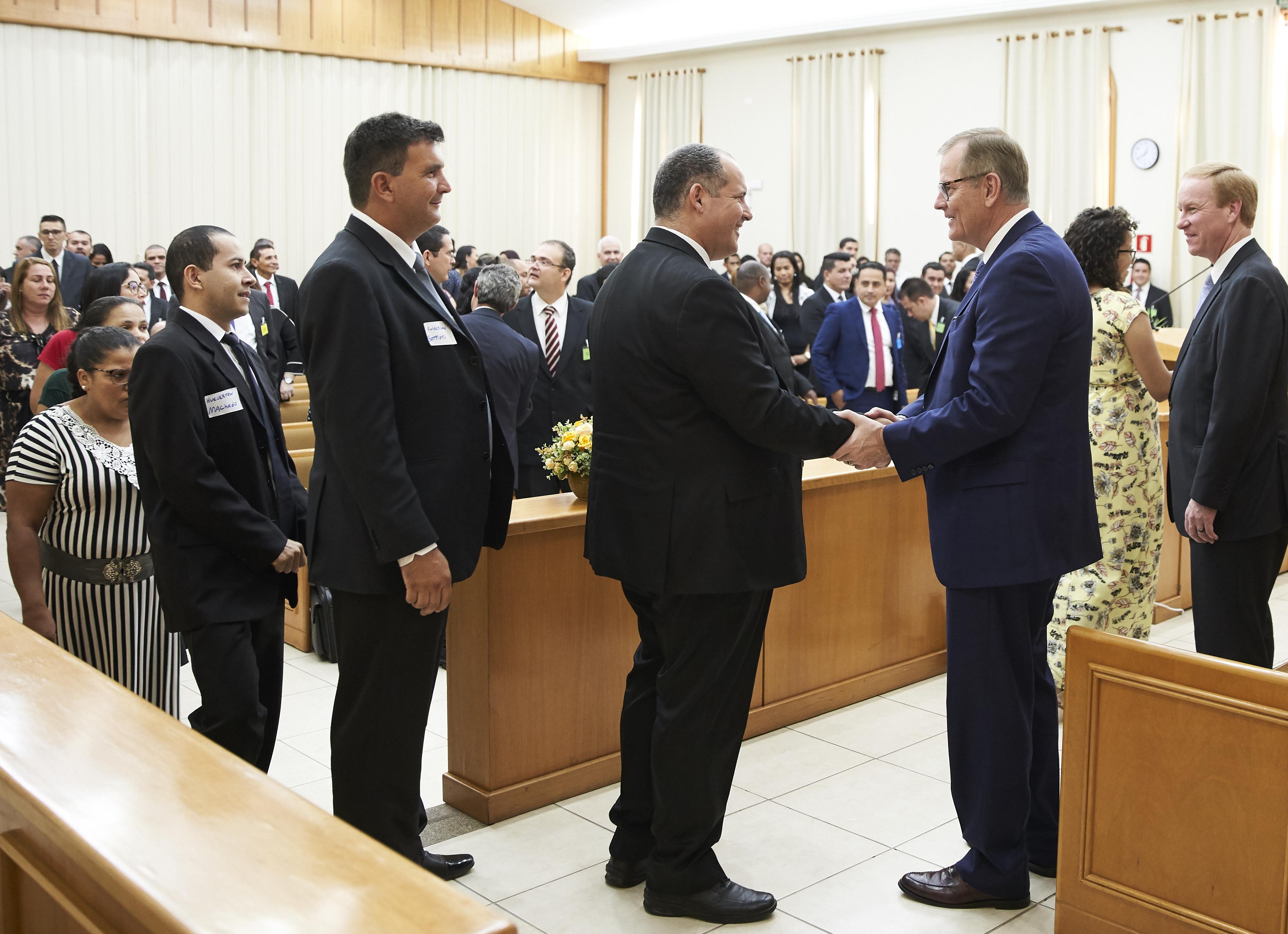 Elder Gary E. Stevenson and Elder W. Mark Bassett greet members at a leadership conference in Cuiaba, Brazil.