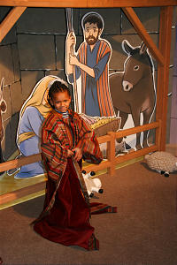 """Four-year-old Elizabeth Mills of West Jordan, Utah, dons a shepherd's robe at interactive Nativity scene at museum's """"I Am a Child of God"""" children's exhibition."""