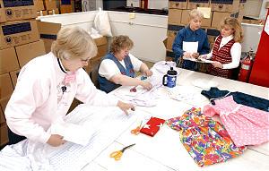 Lynn Burt, Laraine Upwall, Carolyn Barnett and Barbara Hunter volunteer at the Humanitarian Service Room at Deseret Industries in Murray on December 4, 2001.