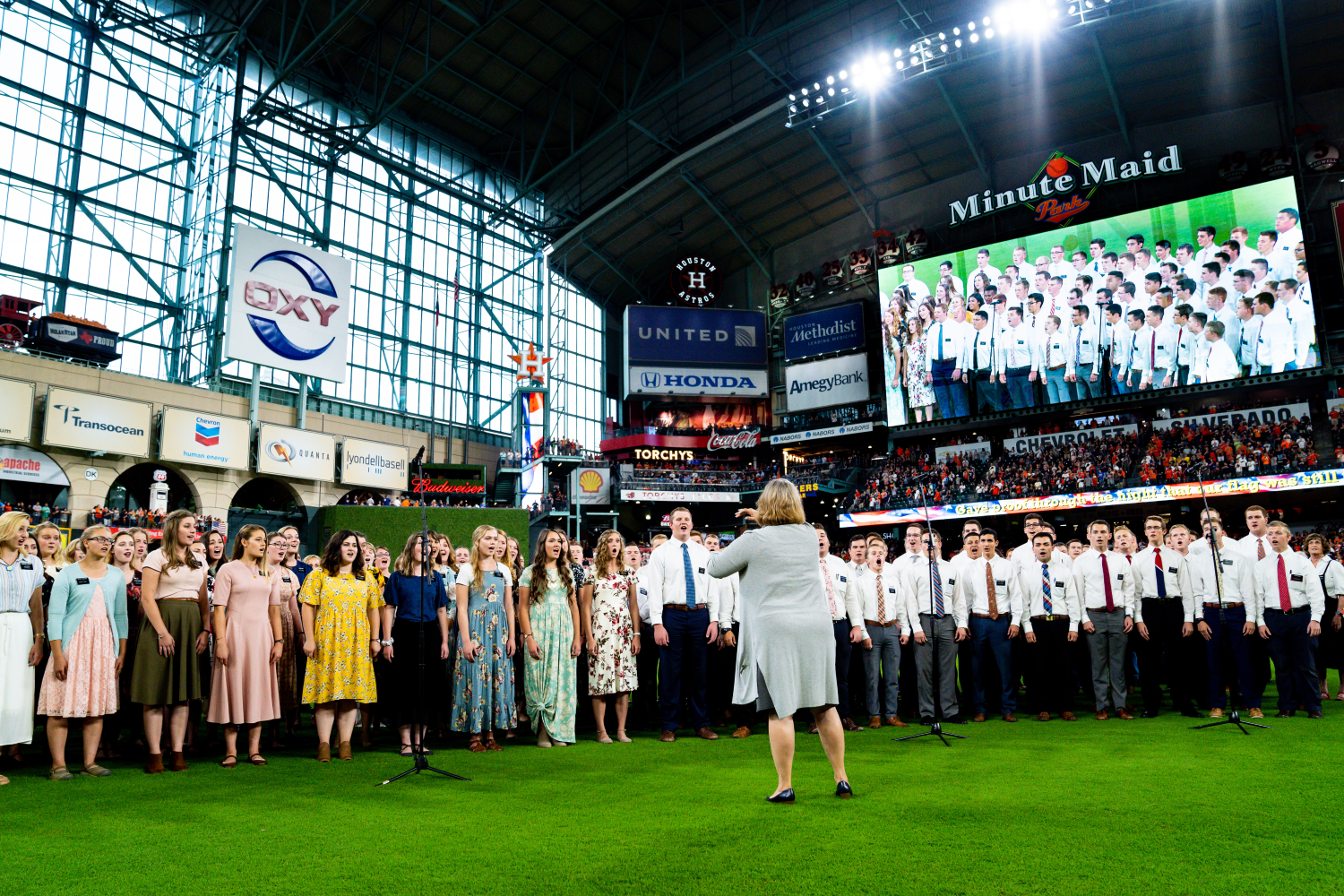 Missionaries from the Texas Houston South Mission choir sing a rendition of the national anthem with April Mecham conducting.