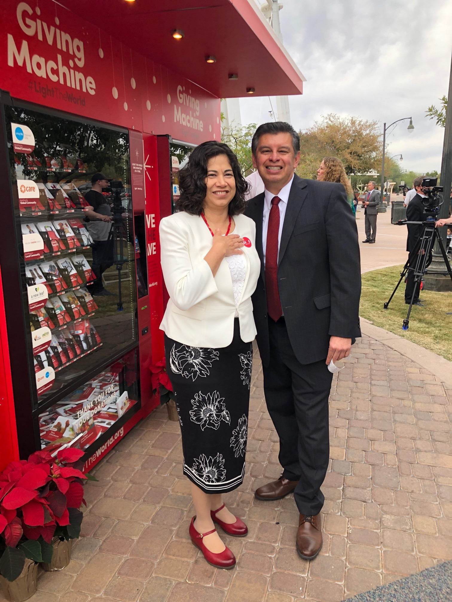 Sister Reyna Aburto of the Relief Society general presidency and her husband, Brother Carlos Aburto, visit with the media following the ribbon-cutting ceremony for giving machines in Gilbert, Arizona. Part of the Church's popular #LightTheWorld campaign, the machines opened in Gilbert on Thursday, Nov. 29.