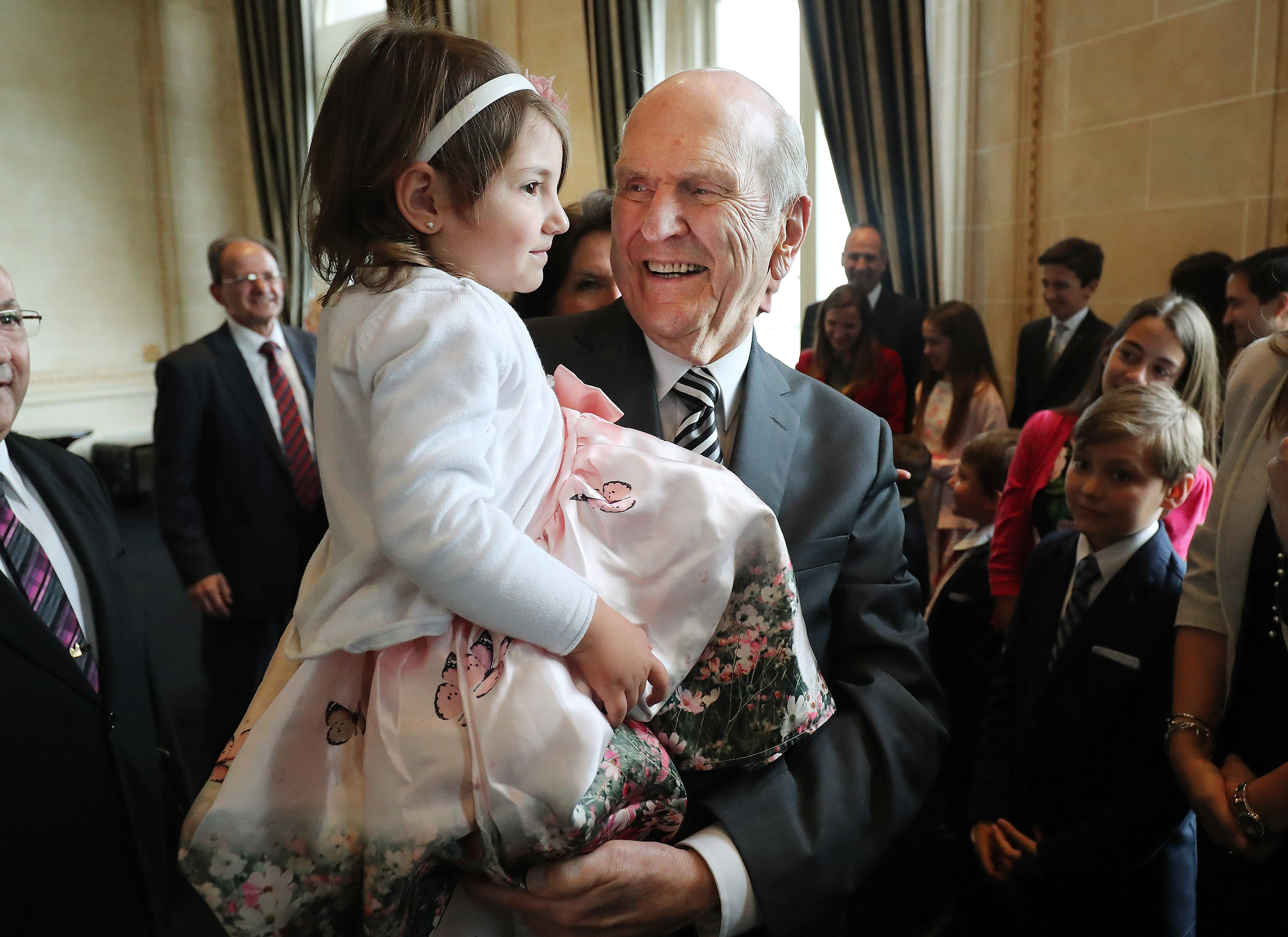 President Russell M. Nelson of The Church of Jesus Christ of Latter-day Saints holds Pierina Risso, 3, while meeting with her three generation LDS family in Montevideo, Uraguay on Thursday, Oct. 25, 2018.