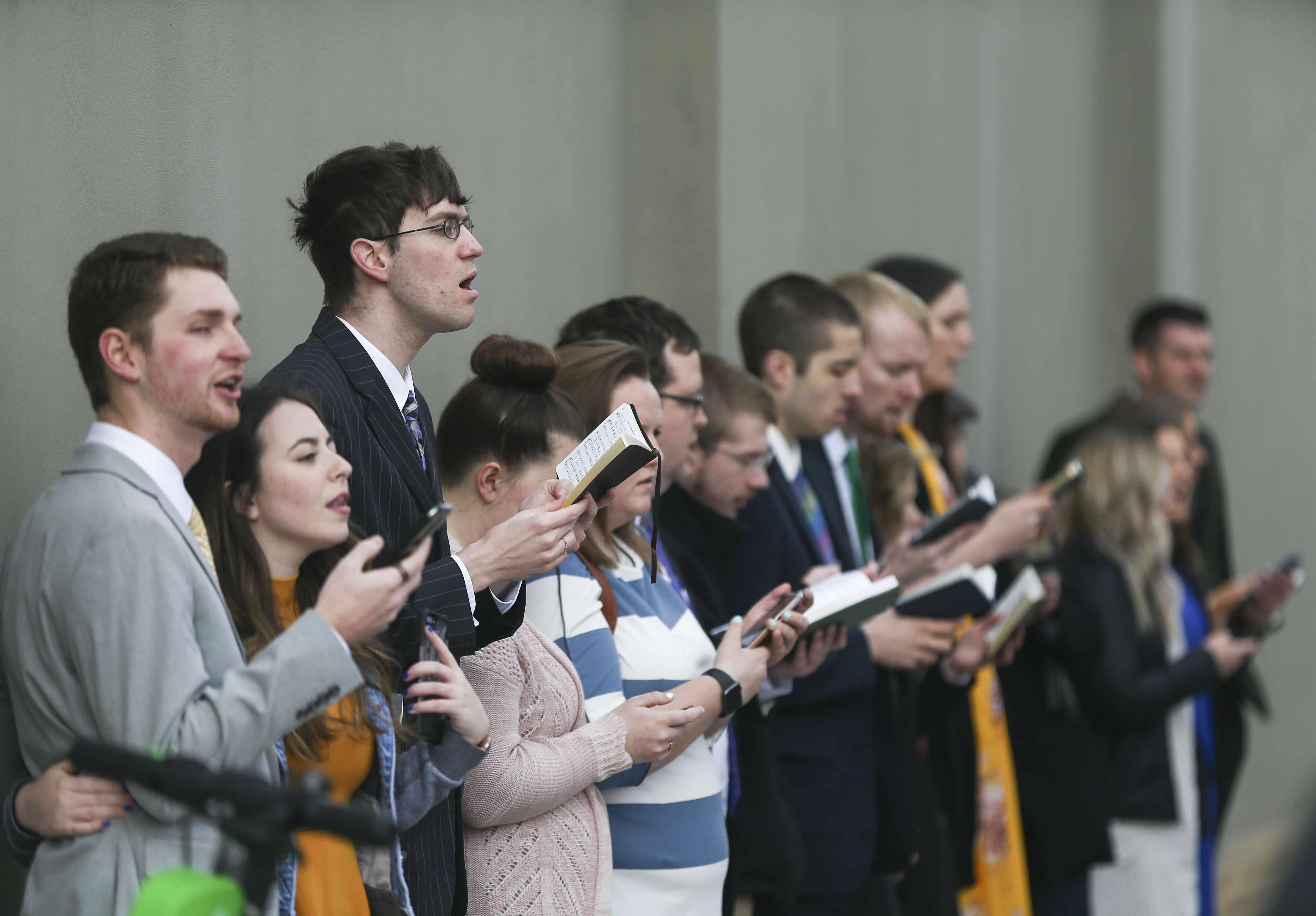 Conferencegoers sing outside the Conference Center before the Sunday morning session of the 189th Annual General Conference of The Church of Jesus Christ of Latter-day Saints in Salt Lake City on Sunday, April 7, 2019.
