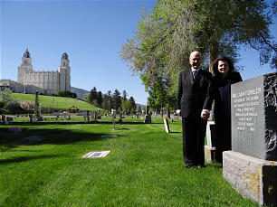 """Elder Russell M. Nelson and Sister Wendy Nelson stand in the city cemetery at Manti, Utah, near the grave of William Fowler, who wrote the hymn text to """"We Thank Thee, O God, for a Prophet."""" Manti Utah Temple is in background."""