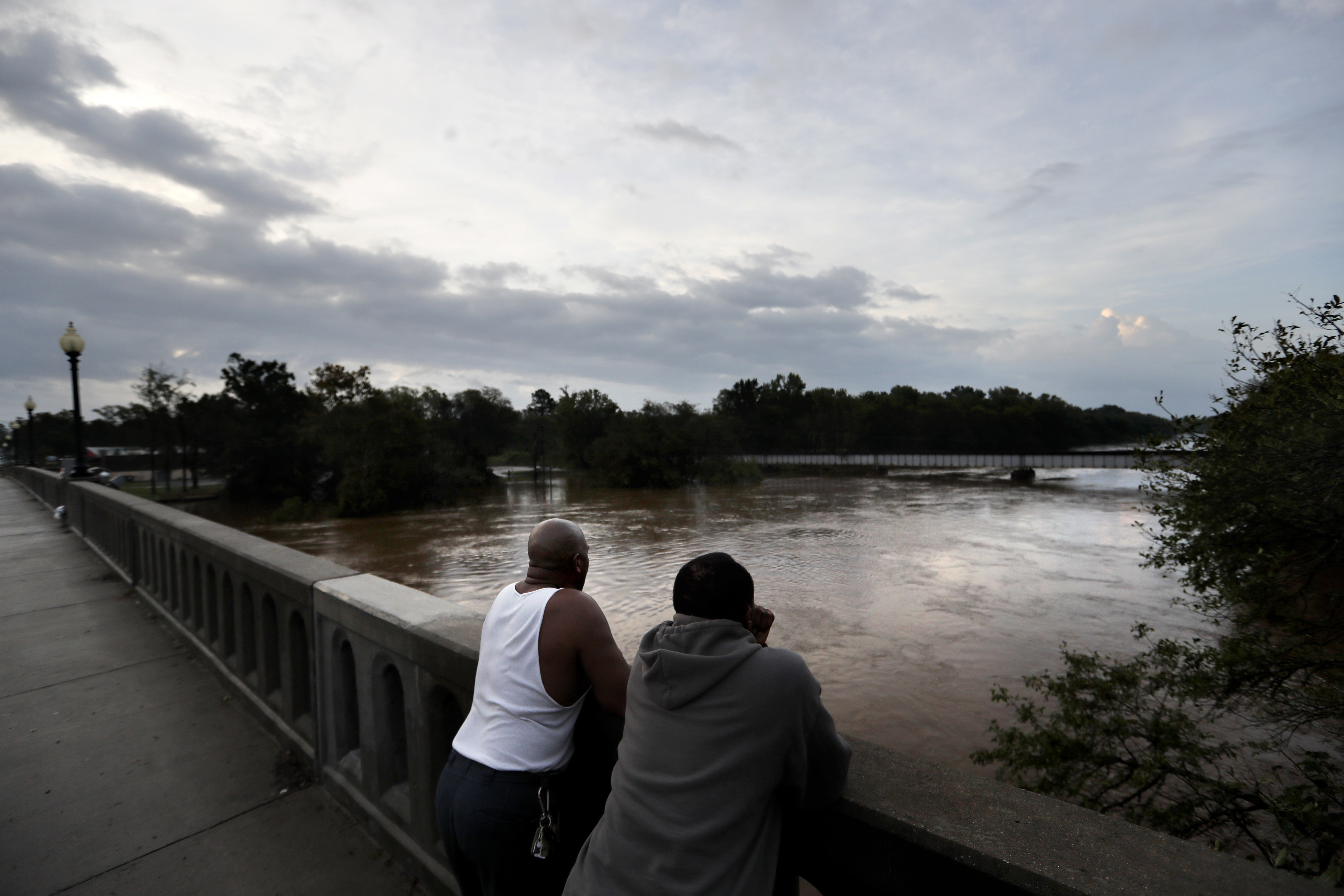 Gerald Generette, right, and Maurice Miller look onto the Cape Fear River as it continues to rise in the aftermath of Florence in Fayetteville, N.C., Monday, Sept. 17, 2018.