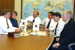 From left are Marvin K. Gardner, Jane Ann Peter, J. Scott Knudson, Richard M. Romney, Don Searle and Bruce Muir. Map in background portrays translations of Book of Mormon. (Submission date: 10/28/2002)