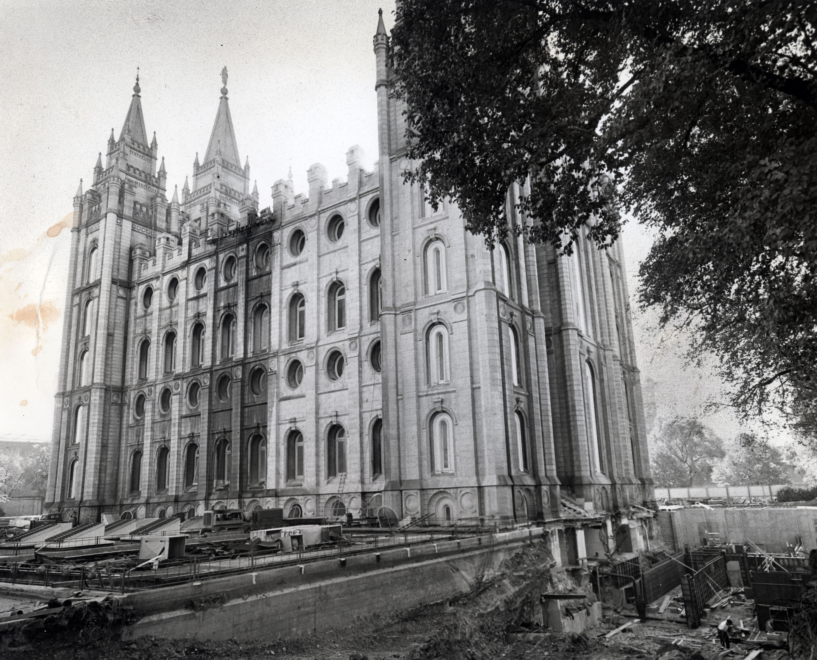 Crews of cleaners remove the patina of age from granite walls of the Salt Lake Temple on Nov. 3, 1962, to match the new granite of the sealing room annex soon that would be added on the north side of the temple. Water from cleaning equipment adds contrast to a section of wall receiving the new look.