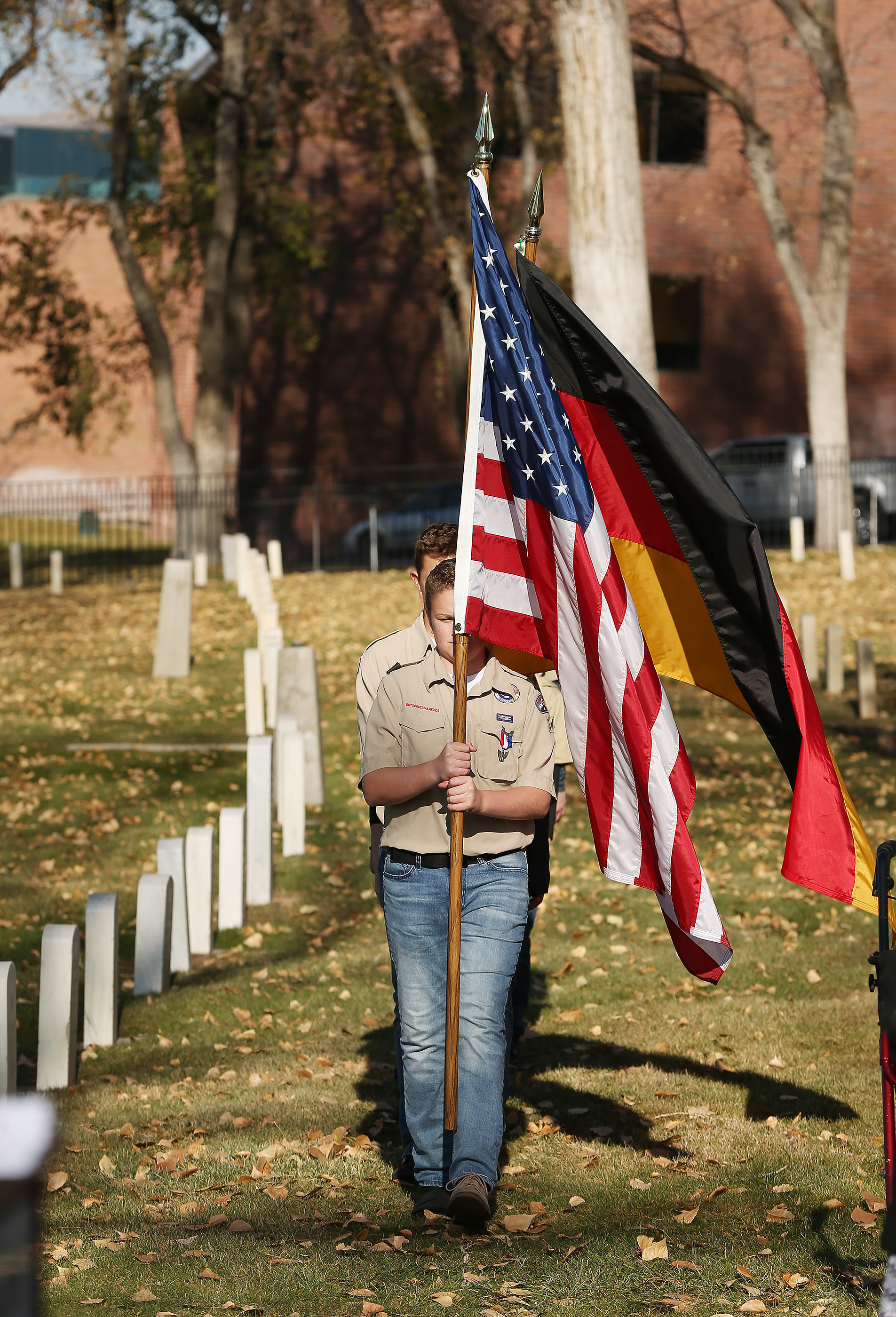 Combined troops of Kaysville Boy Scouts carry the American flag and German flag during the German Day of Remembrance (Volkstrauertag) at Fort Douglas Military Cemetery in Salt Lake City on Sunday, Nov. 18, 2018.