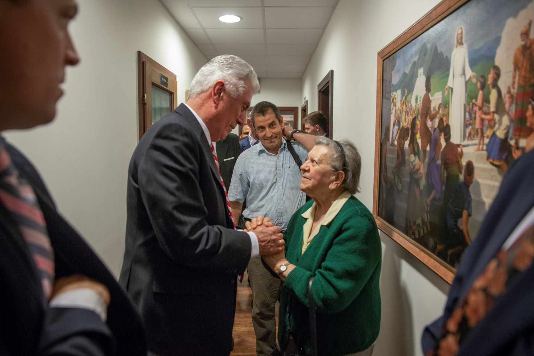 In Gdansk, Poland, for a meeting with branch members and missionaries of the Poland Warsaw Mission, Elder Dieter F. Uchtdorf of the Quorum of the Twelve Apostles stops to visit with a woman in a hallway on Sept. 17, 2018.