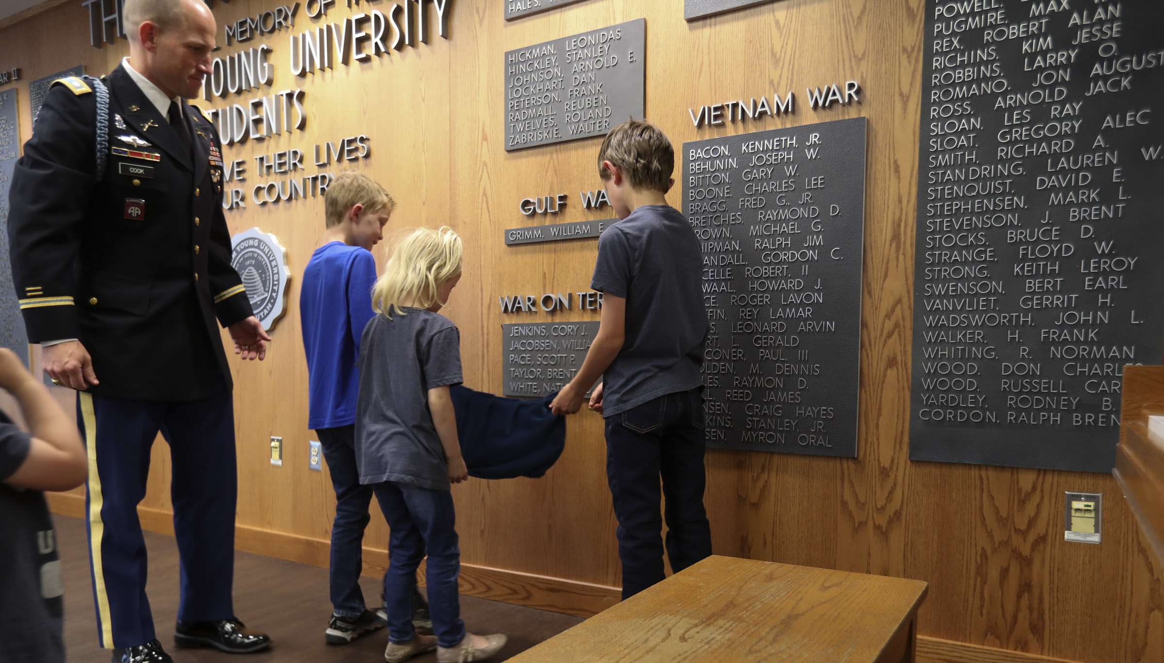 Three of Maj. Brent Taylor's children — Jacob, Eleanor and Alex — unveil a plaque containing his name on the Reflection Room Memorial Wall in the Wilkinson Center during a ceremony on the BYU campus in Provo on Thursday, May 23, 2019. Taylor was killed in Afghanistan in 2018.
