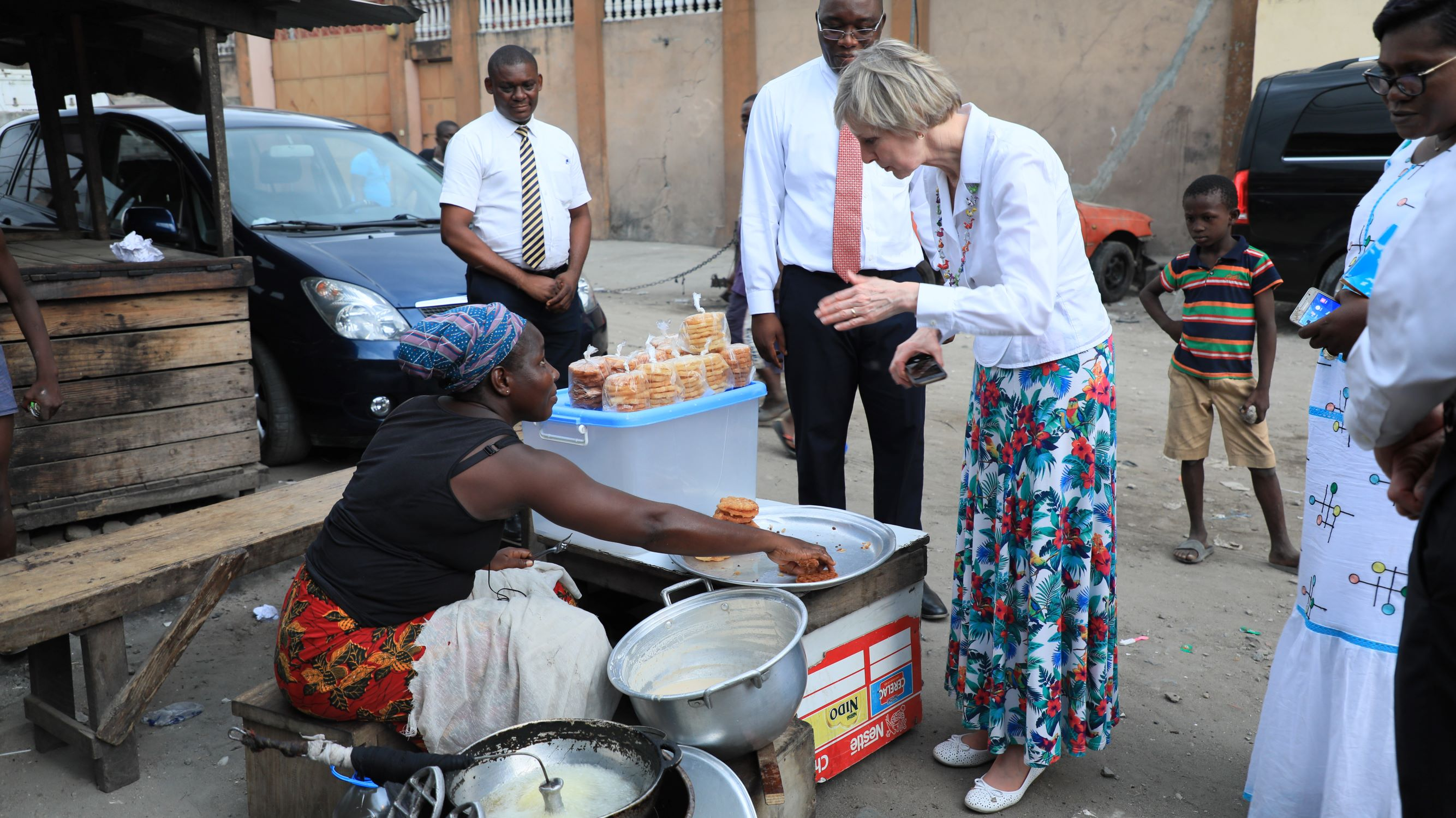 Sister Jean B. Bingham, Relief Society general president, takes a cooking lesson from a woman on the street in Abidjan, Côte d'Ivoire, Friday, March 8, 2019.