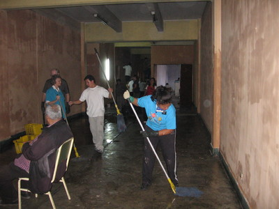 Missionaries hard at work cleaning and painting the inside of a homeless shelter.