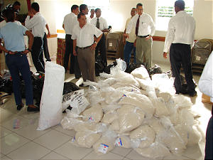 Priesthood leaders and others from the Las Caobas Dominican Republic Stake gather around 15-pound bags of rice that were to be distributed to flood victims. Each bag can provide a typical family sustenance for a week.