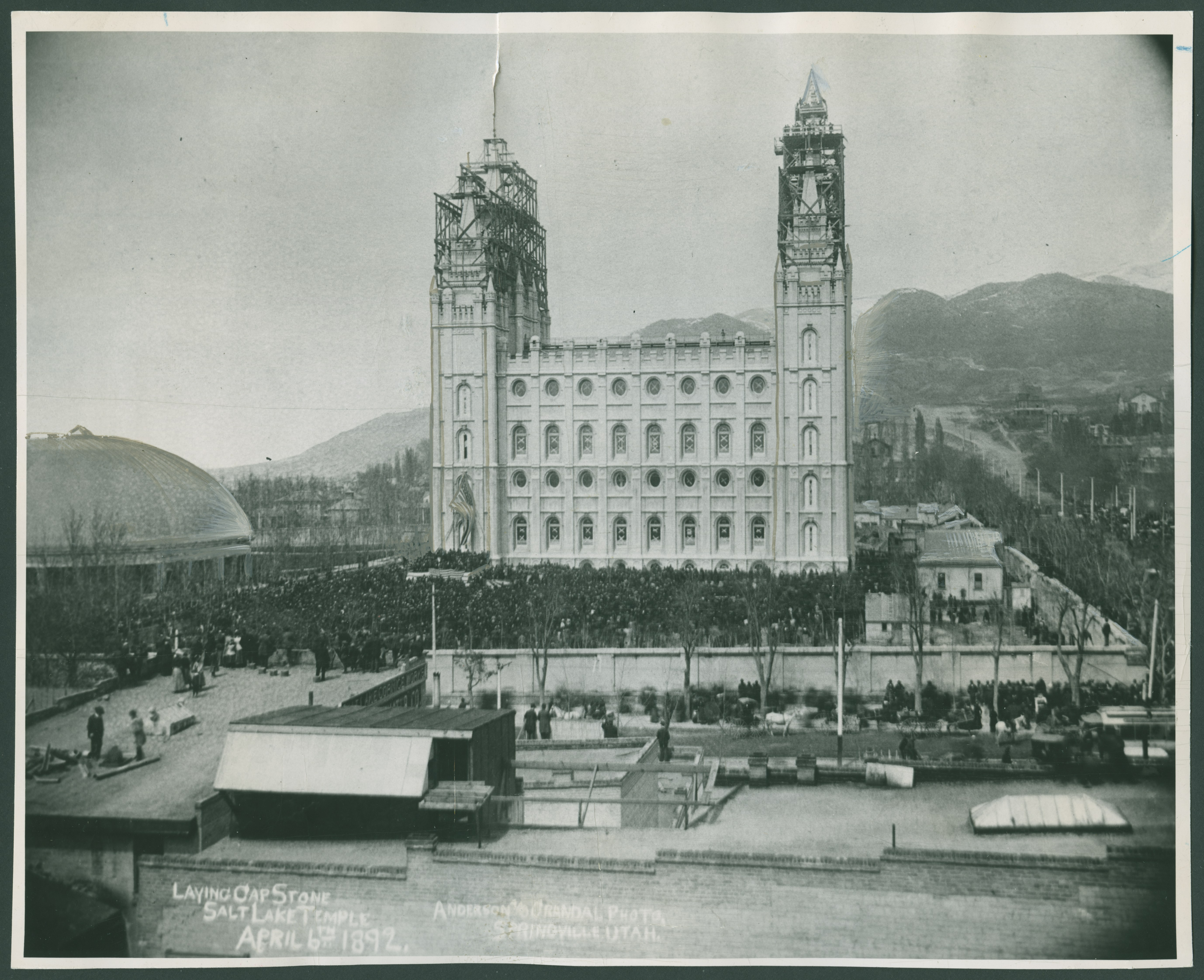 The Salt Lake Temple nearing completion with a large crowd assembled for the capstone-laying ceremony. The temple was dedicated in April 1893.