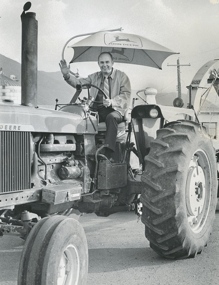 President Dallin H. Oaks of Brigham Young University demonstrates his prowess at driving a tractor when administrative officials were guests at the university's 700-acre farm near Spanish Fork. They toured the milking parlor, granary, calf corrals, orchards and other facilities. The visit concluded with an all-farm picnic.