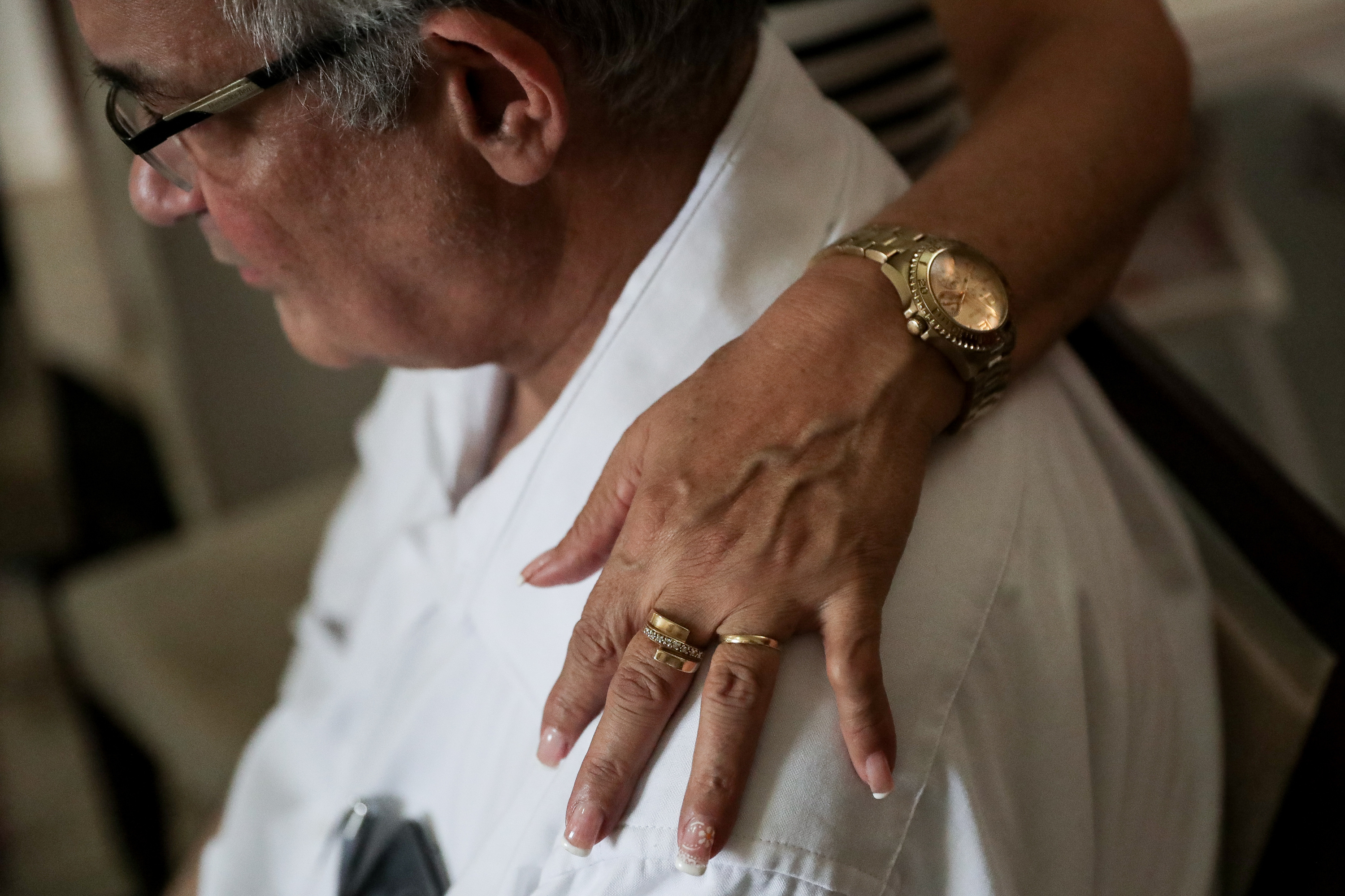 Iracema Saihg rests her hand on her husband, Paulo Almeida Saihg's, shoulder while he recalls long bus journeys to visit the Sao Paulo temple in their high-rise apartment in Recife, Brazil, on Saturday, May 26, 2018.