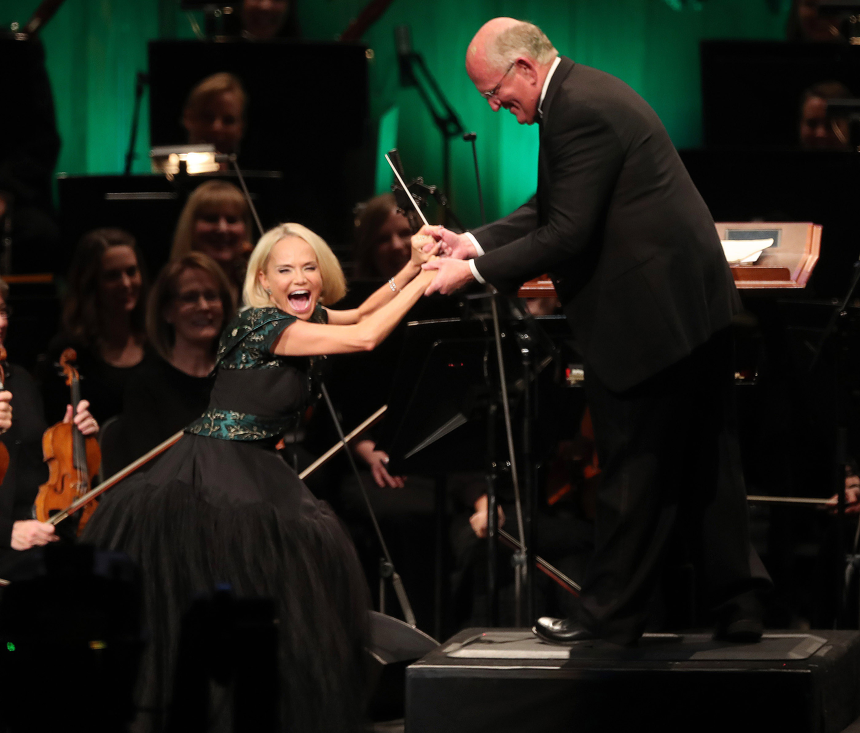 Kristin Chenoweth jokes with conductor Mack Wilberg while singing with the Tabernacle Choir at Temple Square during their opening Christmas concert at the Conference Center in Salt Lake City on Thursday, Dec. 13, 2018.