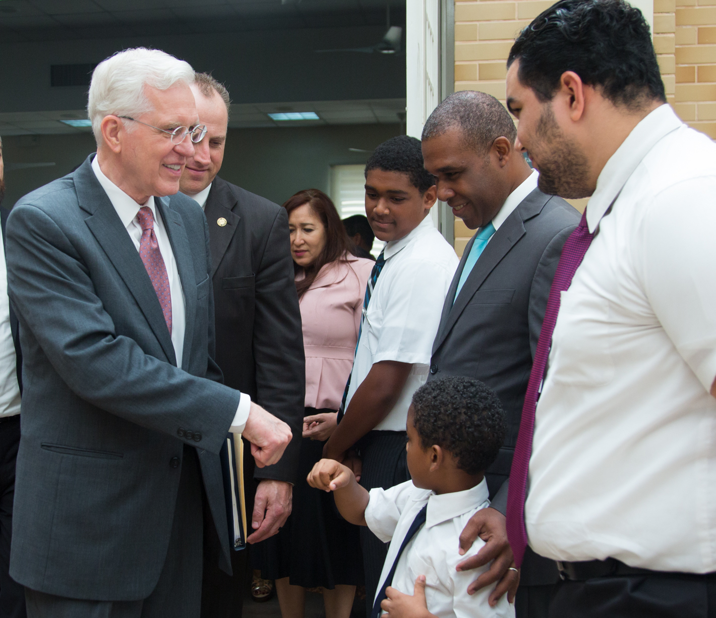Elder D. Todd Christofferson fist bumps a little boy following a meeting on Nov. 11, 2018, with the Santo Domingo Dominican Republic San Geronimo Stake.