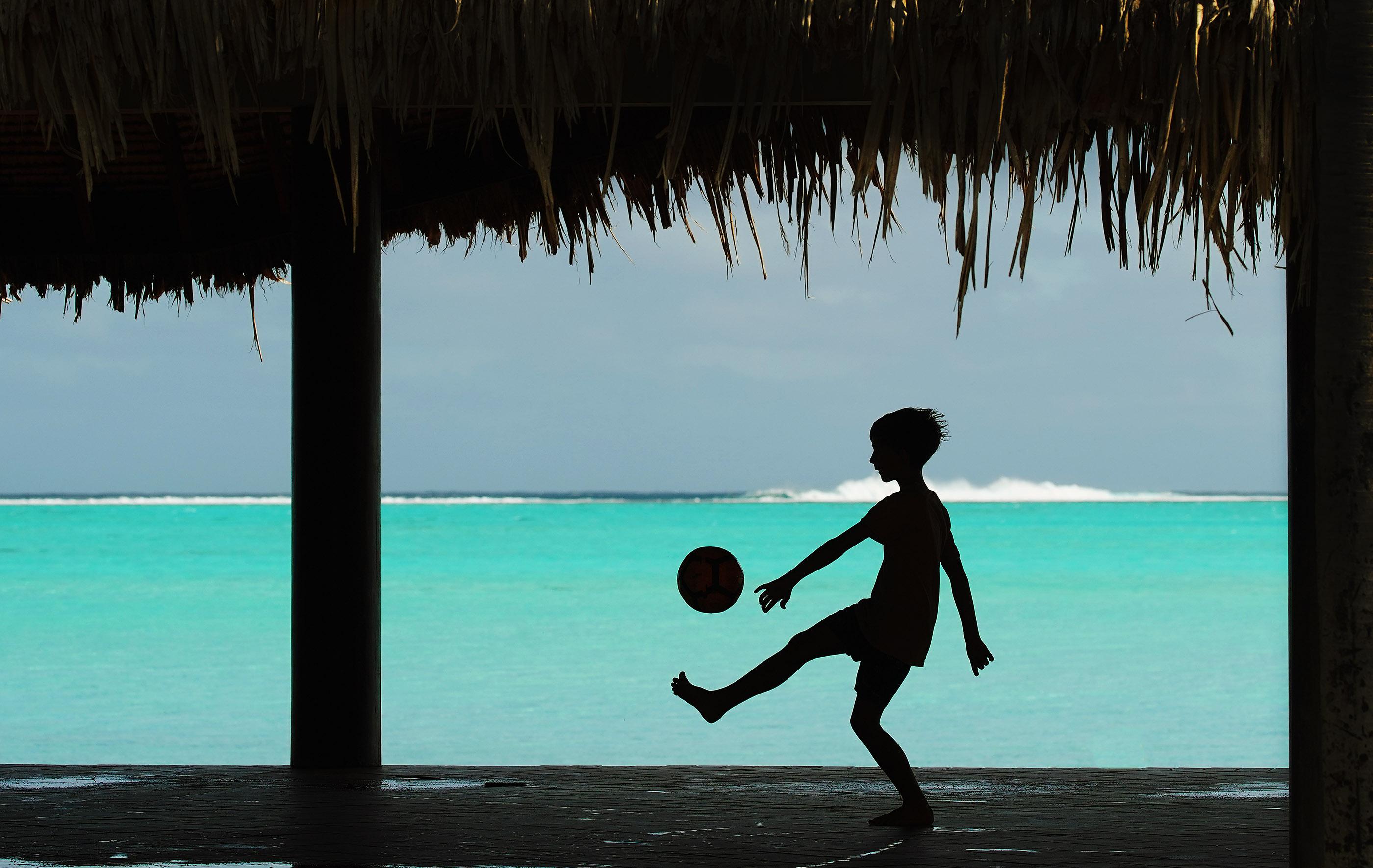 A boy plays with a soccer ball near the beach in Bora Bora on May 27, 2019.