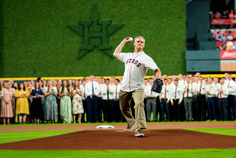 Elder David A. Bednar throws the first pitch, a strike.