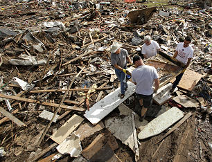 Men carry what remains of a piano through the rubble at a tornado-ravaged home in Moore, Okla. No Church members were killed in the catastrophe that claimed 24 lives.