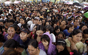 Flood affected residents gather for relief goods in suburban Marikina, east of Manila, Philippines on Tuesday, Aug. 14, 2012.
