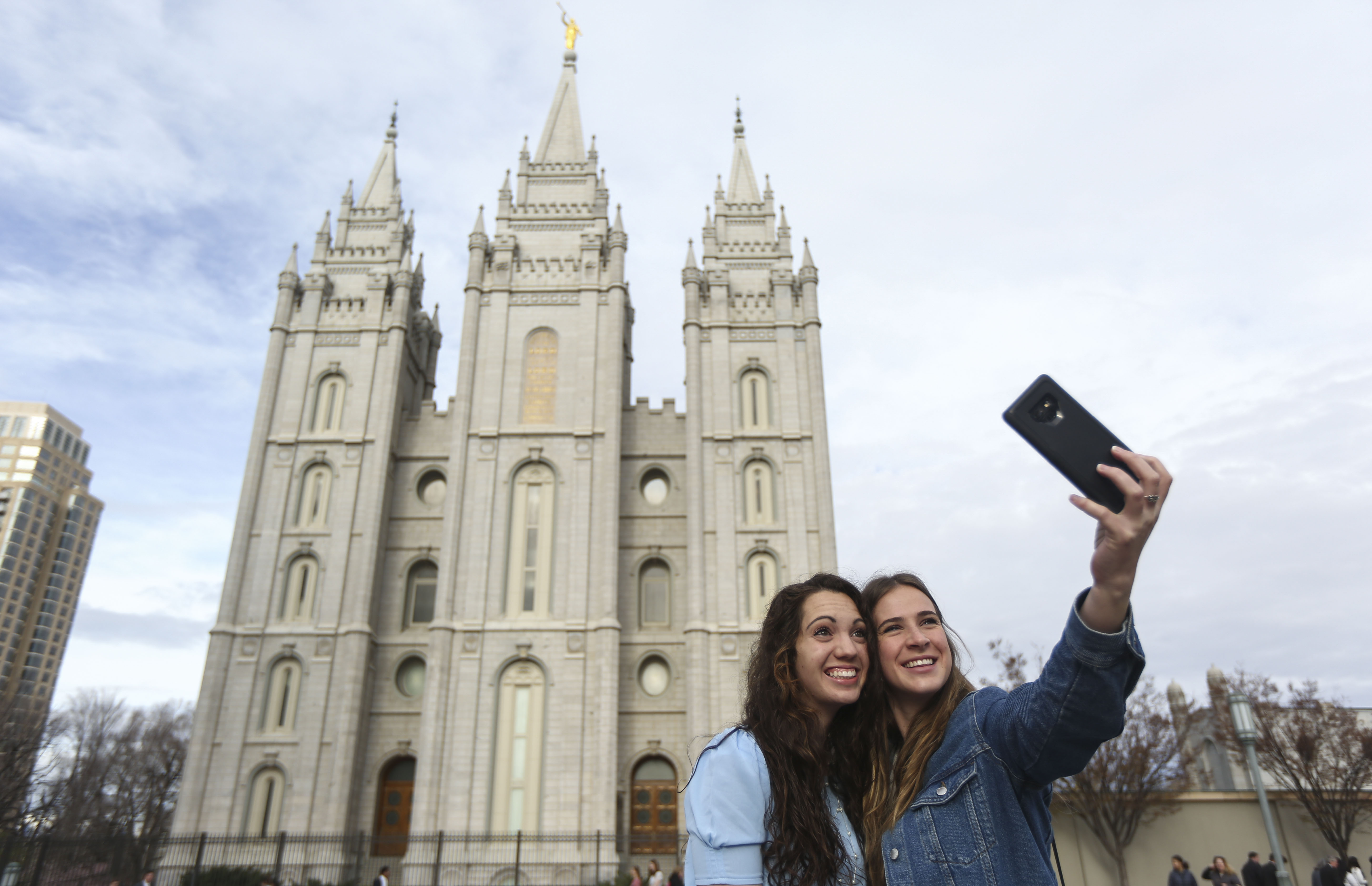 Mika Katich, of Auburn, Ala., and Chelsey Campbell, of California, take a selfie in front of the Salt Lake Temple as conferencegoers arrive at the Conference Center for the Sunday morning session of the 189th Annual General Conference of The Church of Jesus Christ of Latter-day Saints in Salt Lake City on Sunday, April 7, 2019.
