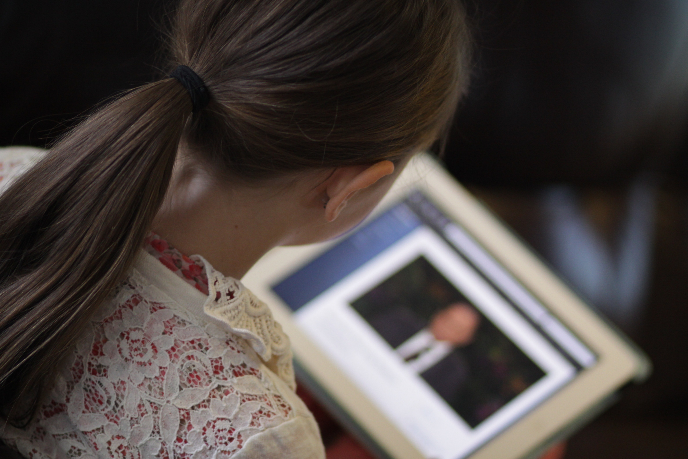 A young girl watches general conference on a tablet.
