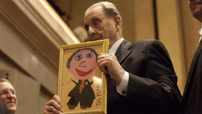President Thomas S. Monson has a present given to him by a member of the audience. The picture is the self portrait of a young girl.