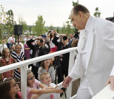 President Thomas S. Monson pauses to shake hands with members as he leaves the cornerstone area of Kansas City Missouri Temple on the day of its dedication.