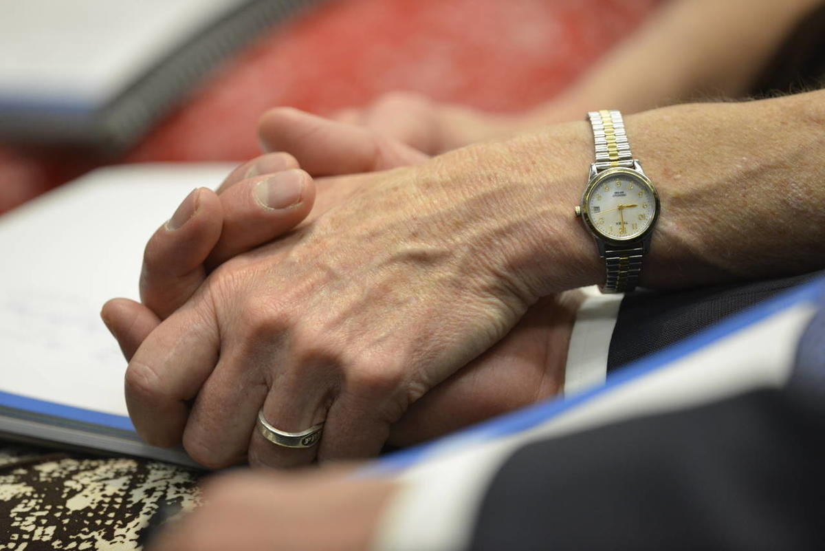 A mission president and his wife hold hands during a session of the 2014 Seminar for New Mission Presidents.