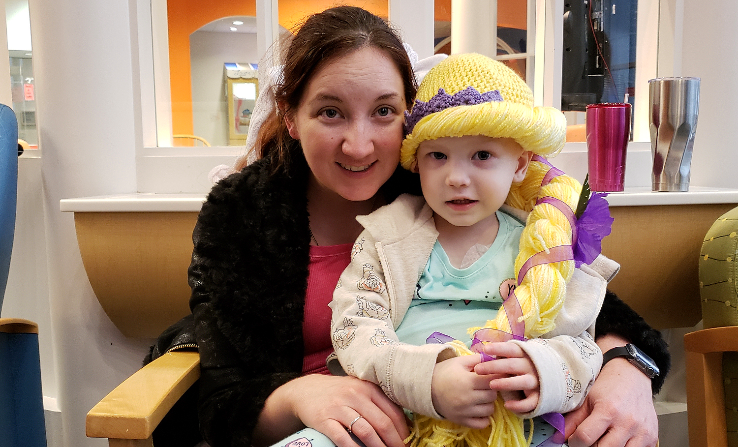 A mom holds her little girl — who is undergoing treatment at the Texas Children's Hospital — as she receives a yarn wig from young women from the Spring Texas Stake.