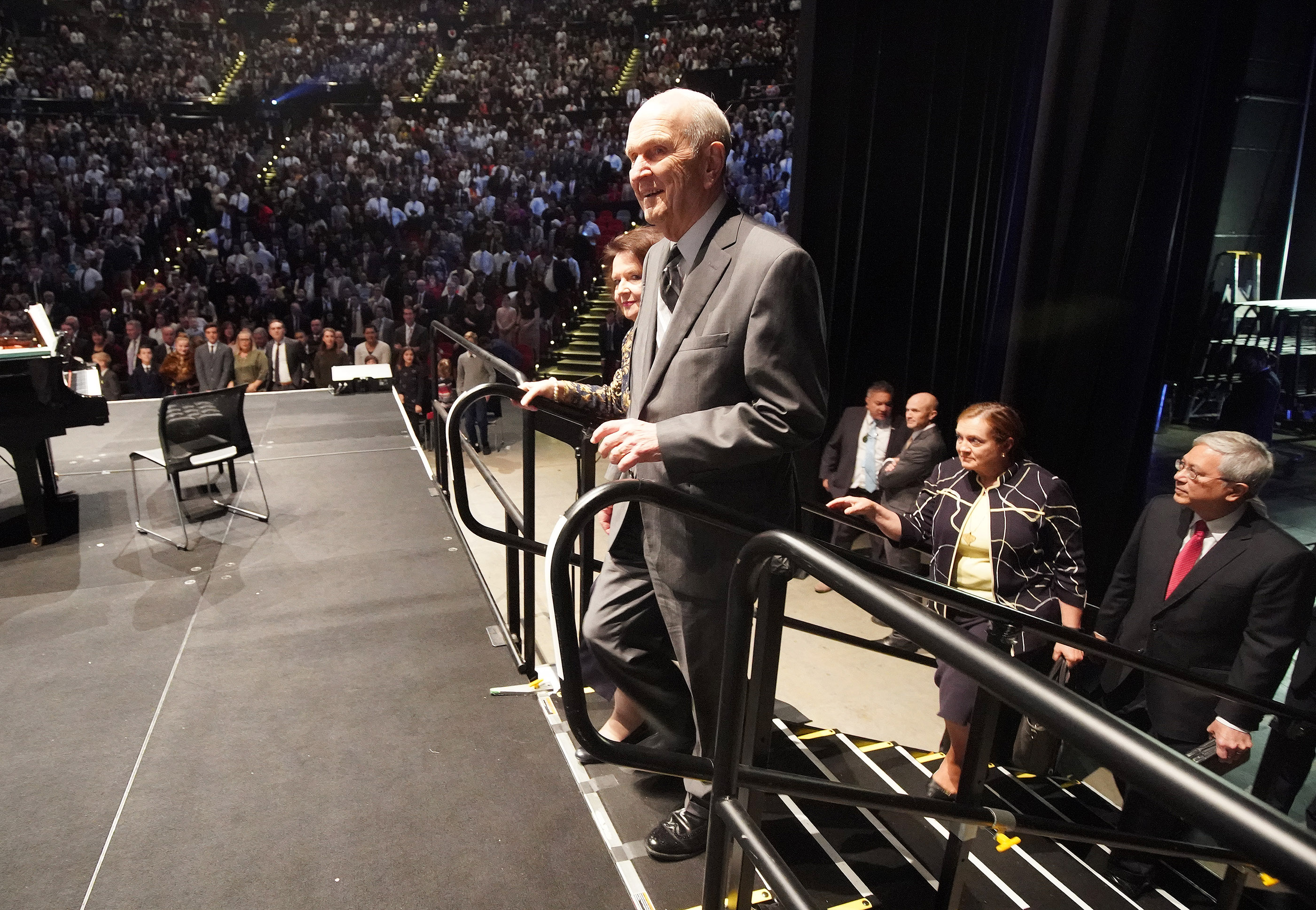 President Russell M. Nelson of The Church of Jesus Christ of Latter-day Saints and his wife, Sister Wendy Nelson, walk on stage at the International Conference Center to speak on May 19, 2019, in Sydney, Australia. Elder Elder Gerrit W. Gong, of The Church of Jesus Christ of Latter-day Saints' Quorum of the Twelve Apostles, and his wife, Sister Susan Gong, follow.