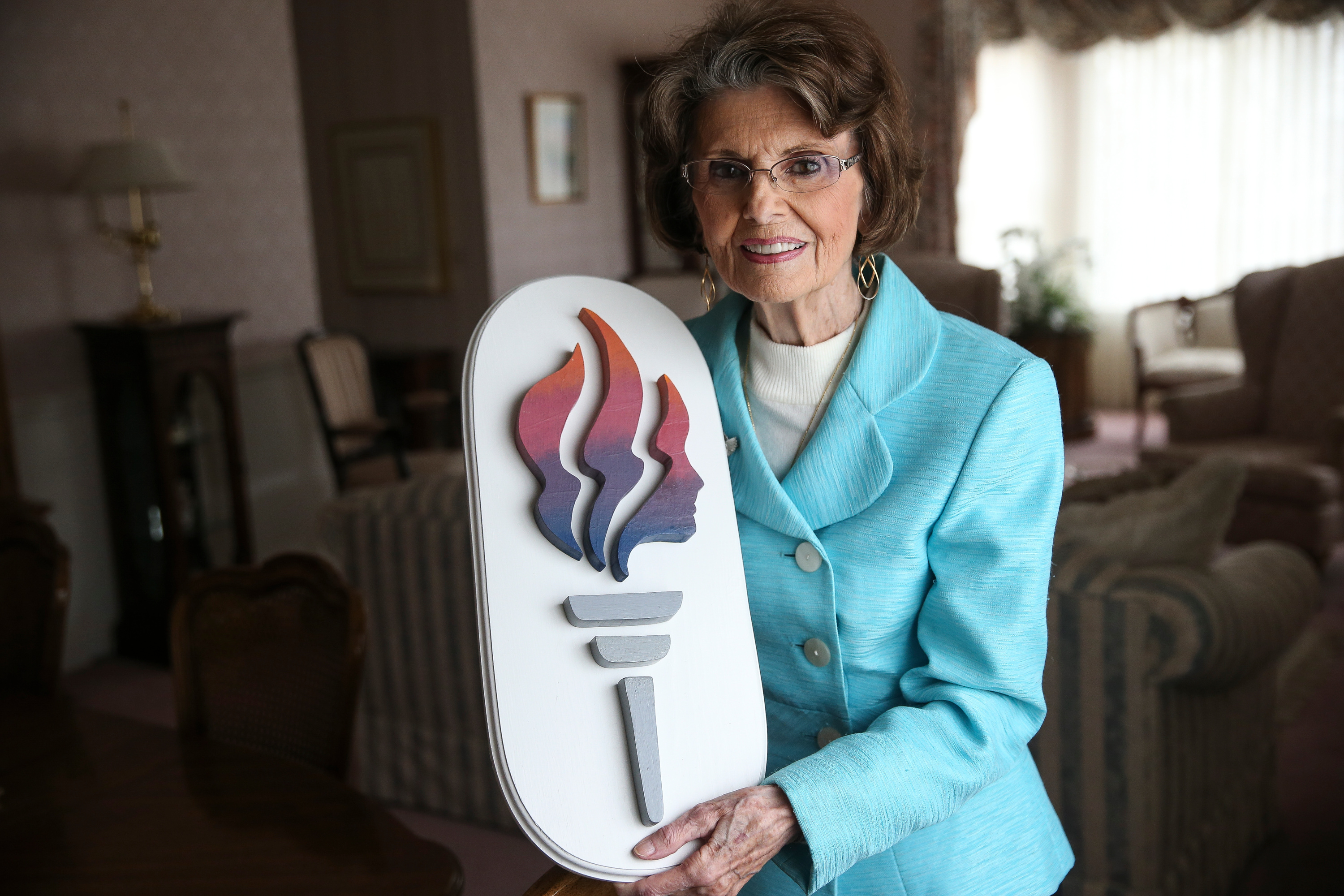 Former LDS Young Women General President Ardeth G. Kapp poses for a photo with a wood Young Women logo at her home in Bountiful on Thursday, Jan. 11, 2018.