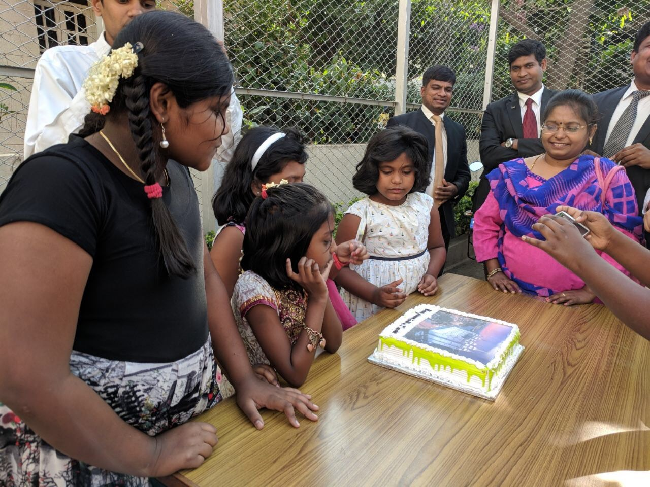 Members in Bengaluru, India, wait to cut a cake with a picture of the Salt Lake Temple to celebrate the announcement of a temple for India following general conference.