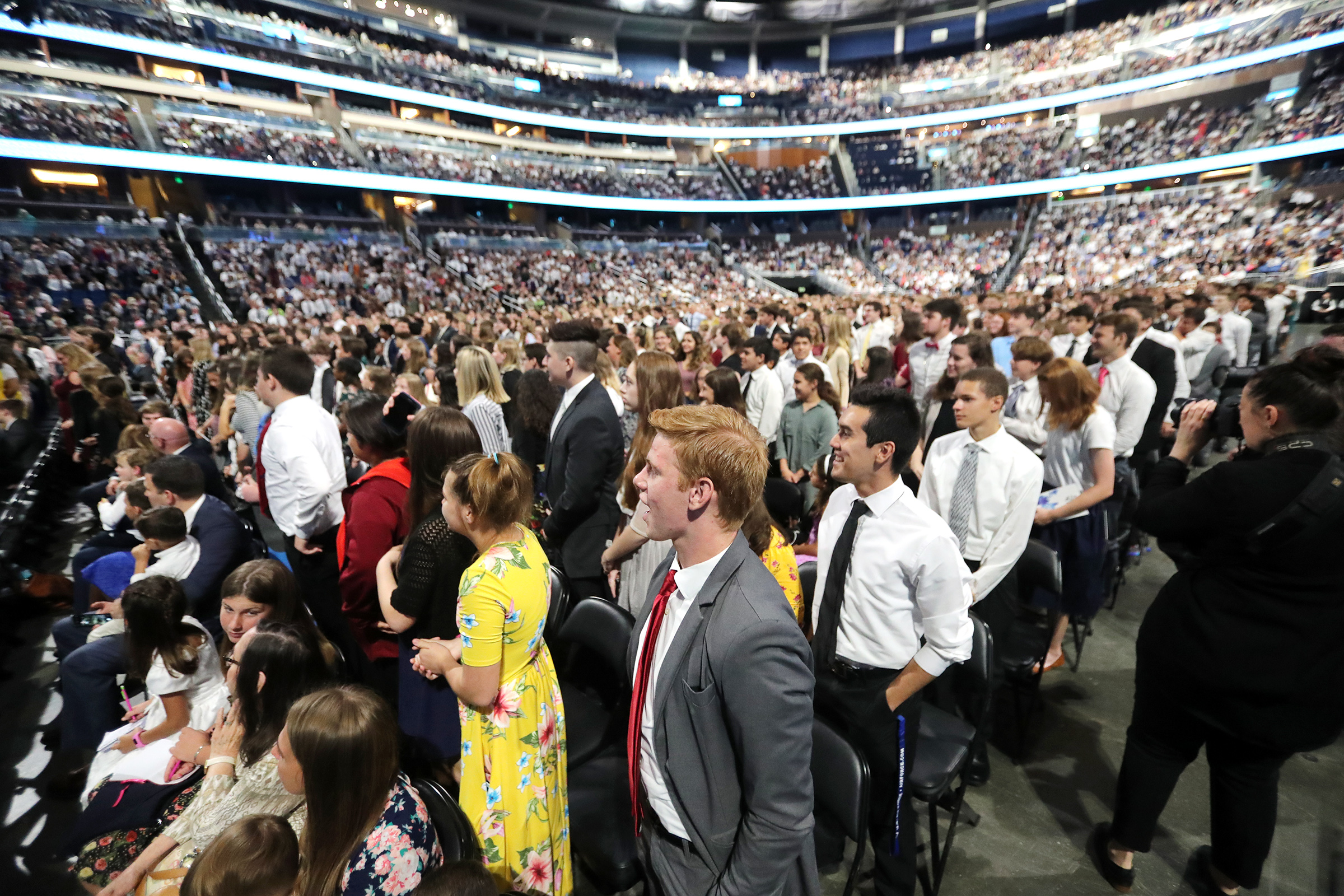 Young men and women stand at the request of President Russell M. Nelson as he speaks during the devotional at the Amway Center in Orlando, Florida, on Sunday, June 9, 2019.